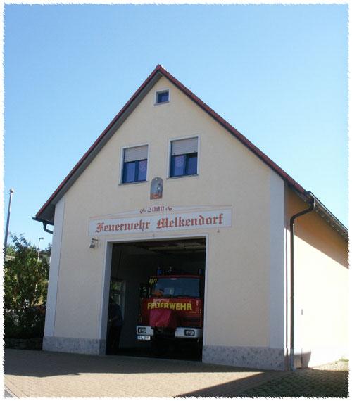 Das Bild zeigt das Melkendorfer Feuerwehrhaus mit geöffnetem Tor und unserem LF8